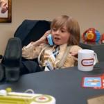 un petit garçon qui caricature le directeur avec sa tasse à café et son téléphone