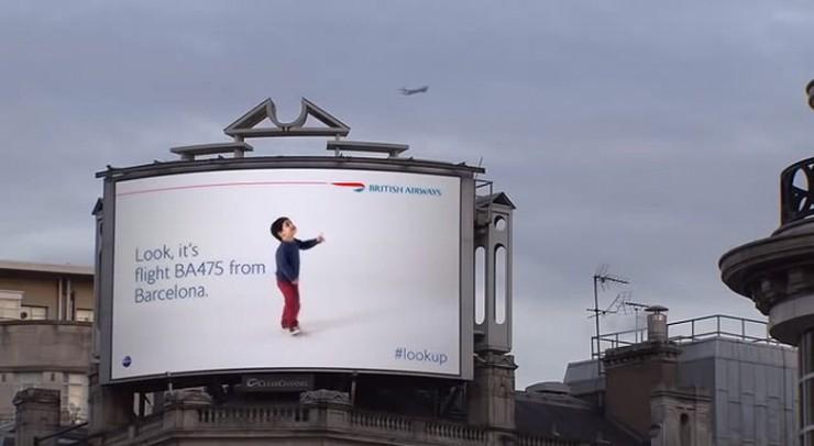 un enfant nous montre du doigt l'avion british airways qui passe au dessus de lui