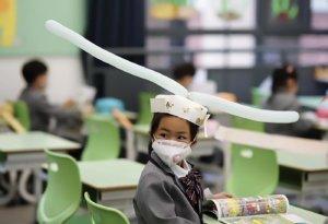 Un accessoire insolite qui impose naturellement aux enfants de rester à l'écart de leurs camarades et qui fait aussi référence aux couvre-chefs portés à l'époque de la dynastie Song